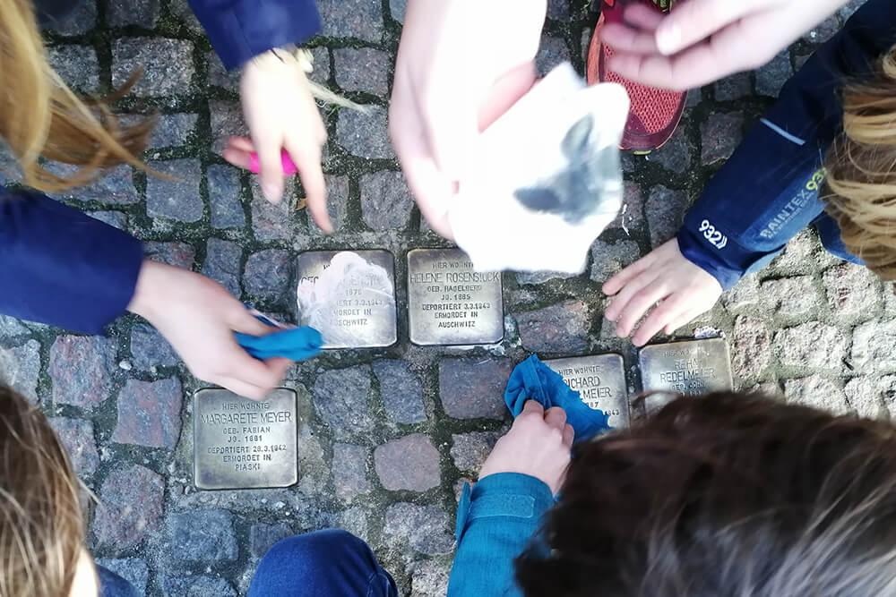 Kinder putzen Stolpersteine in der Yorkstrasse 60 in Berlin