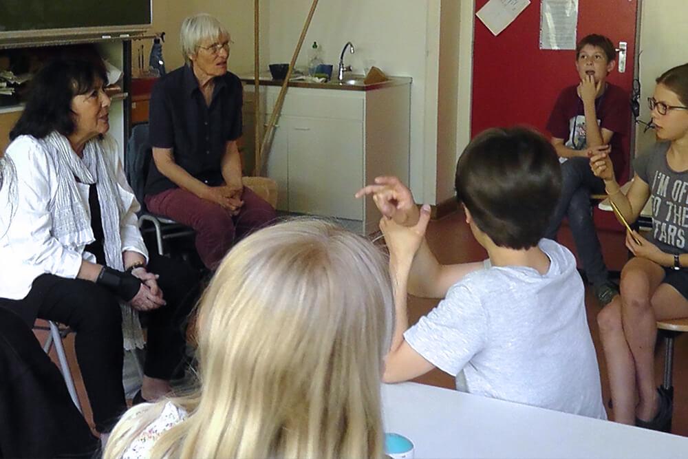 Tana zu Besuch in der Charlotte-Salomon-Grundschule. Sie sitzt mit Kindern in einem Klassenzimmer.